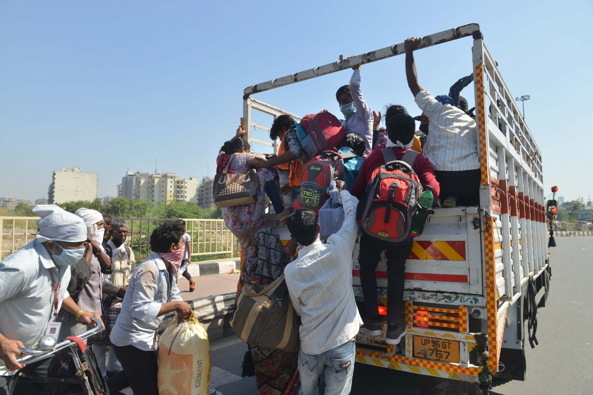 Noida: Migrant workers board a truck in Delhi-UP Border to reach their native places during the extended nationwide lockdown imposed to mitigate the spread of coronavirus, on May 16, 2020. (Photo: IANS)