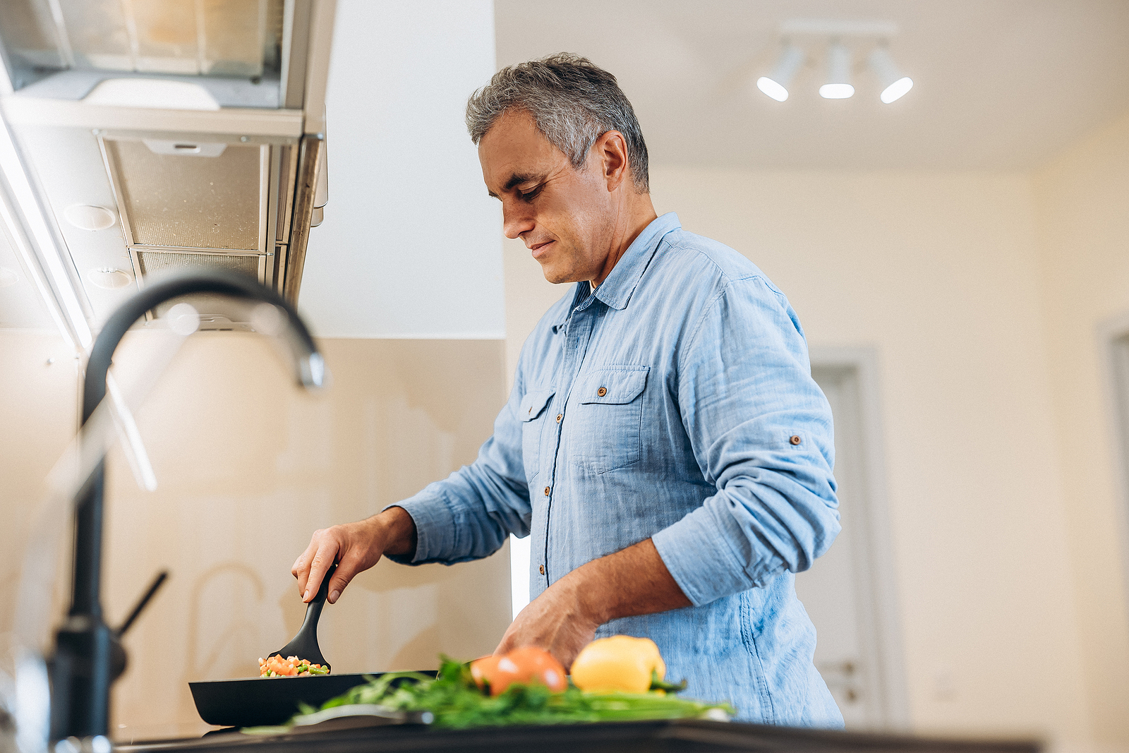 An image depicting a man cooking soyfoods. Research shows soy protein does not negatively effect testosterone levels.