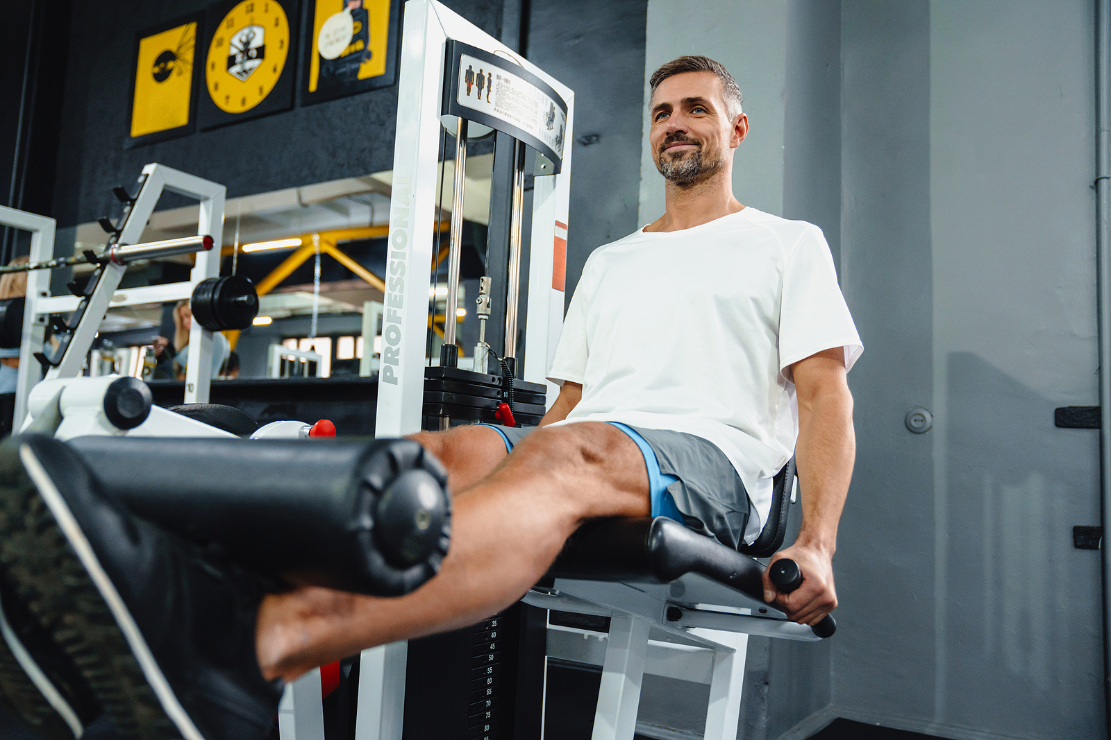 An image depicting a man use a machine at a gym to build muscle mass.