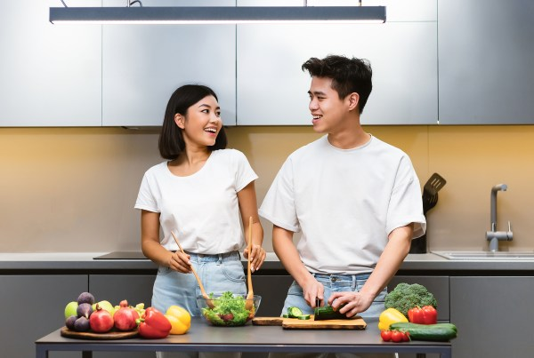 Couple Cooking Healthy Food Making Vegetable Salad Standing In Kitchen At Home