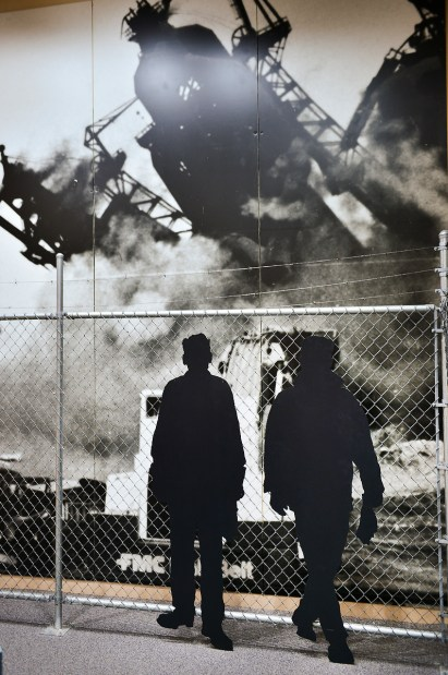 Cutouts of workers watch the demolition of the US Steel blast furnace in 1985.