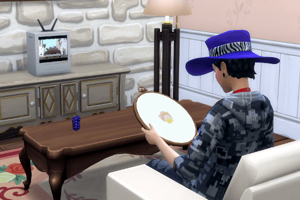 Sims 4 Cottage Living cross stitching while watching TV