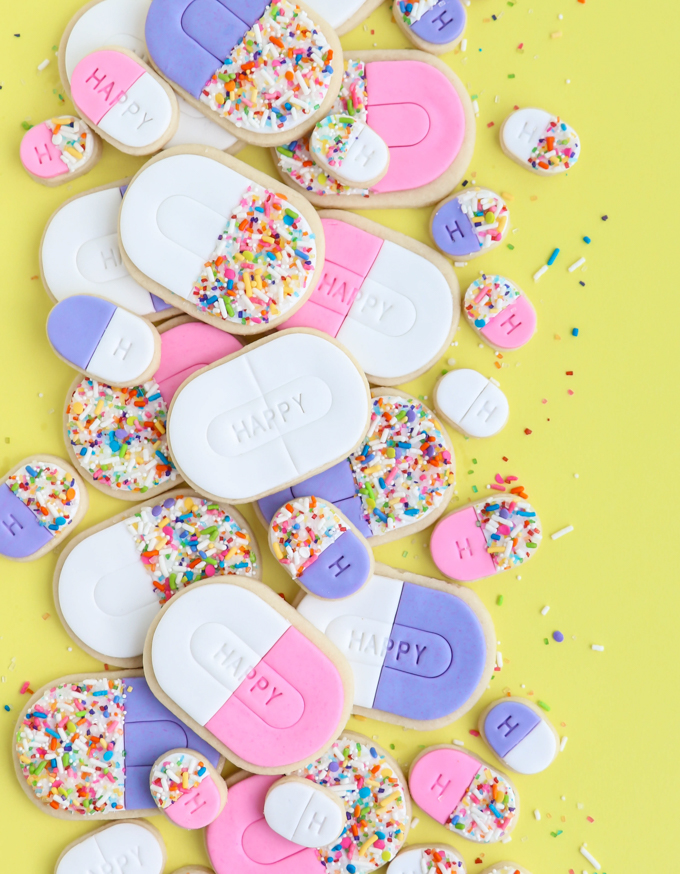 happy pill cookies on yellow backdrop