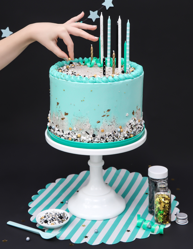 Mint Blue Cookies And Cream Cake On Stand With A Hand Over Top