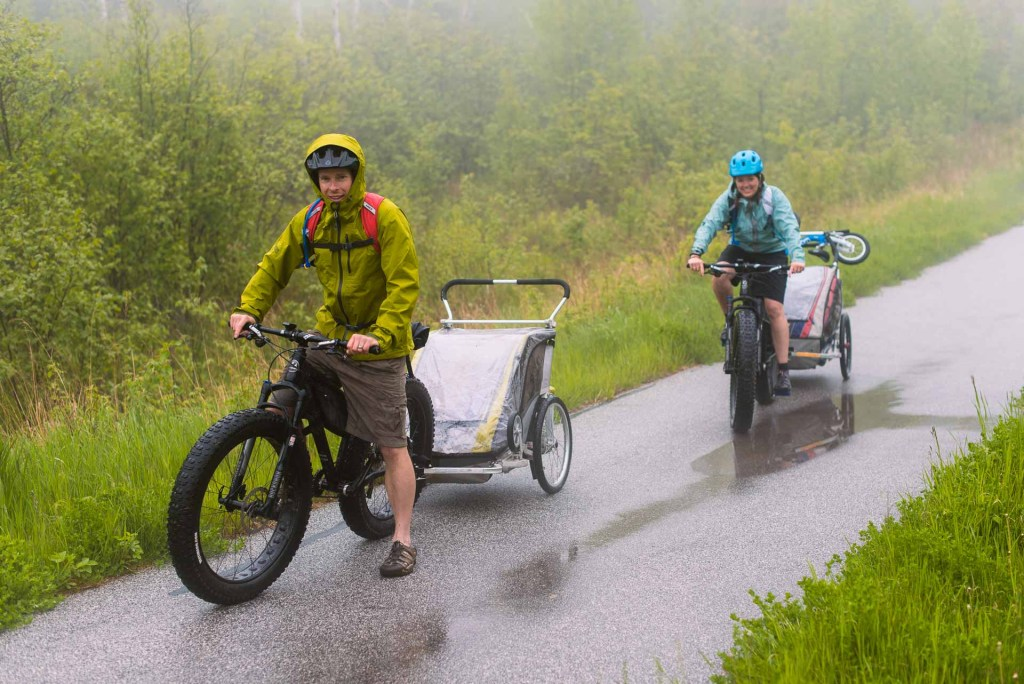 Couple with children riding through the rain on fat tire bikes