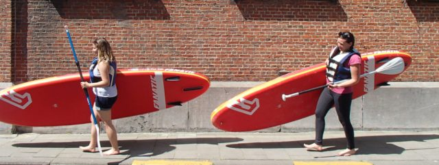 This is an image of two girls carrying stand up paddle boards in Ghent