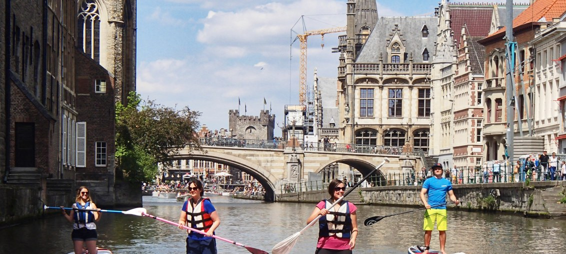 This is an image showing 4 people on a SUP board in Gent