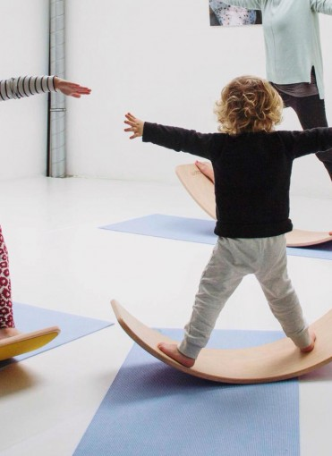 A kid balancing on a wobbel at a yoga class in Ghent