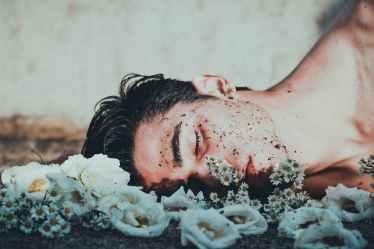 man lying on white flowers