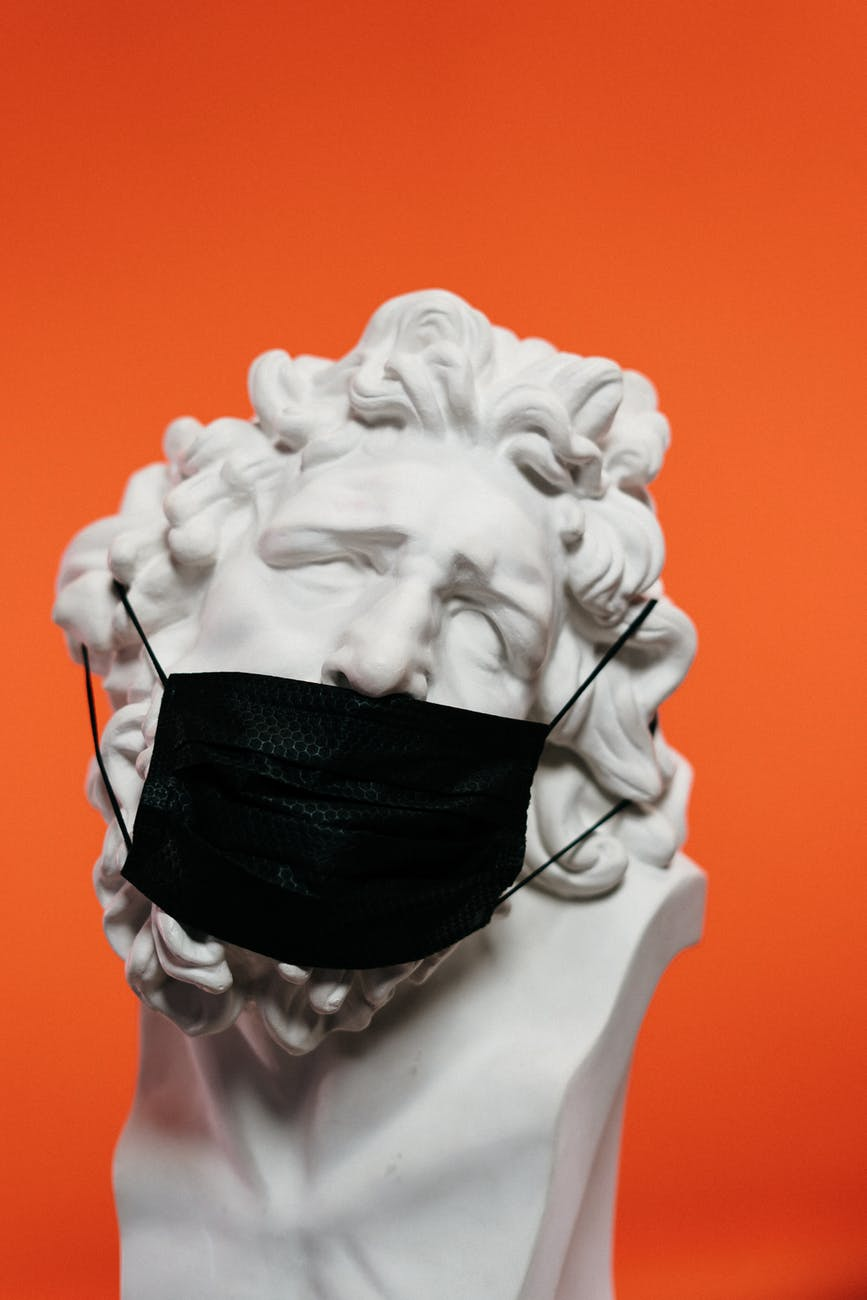 white ceramic sculpture with black face mask