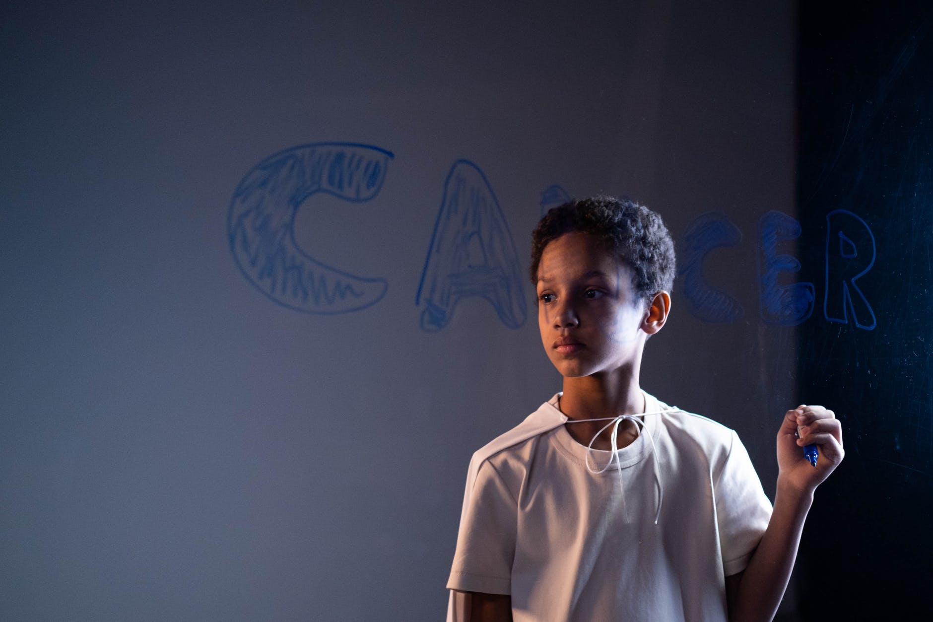 boy in white shirt holding blue marker