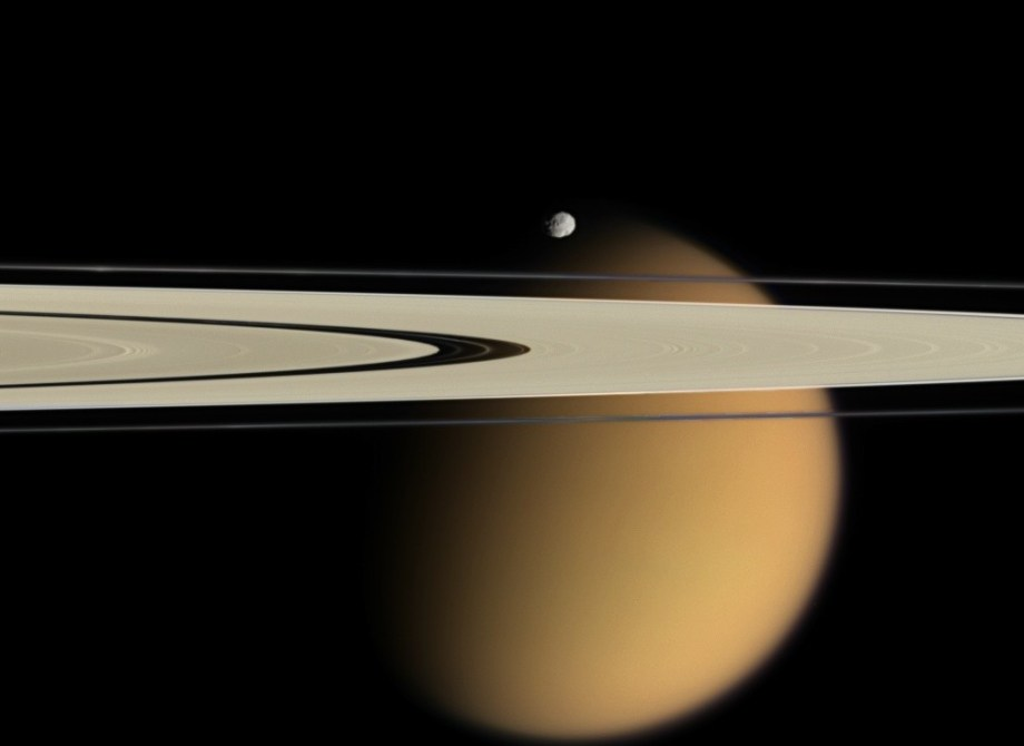 Epimetheus and smog-enshrouded Titan, with Saturn's A and F rings stretching across the scene.