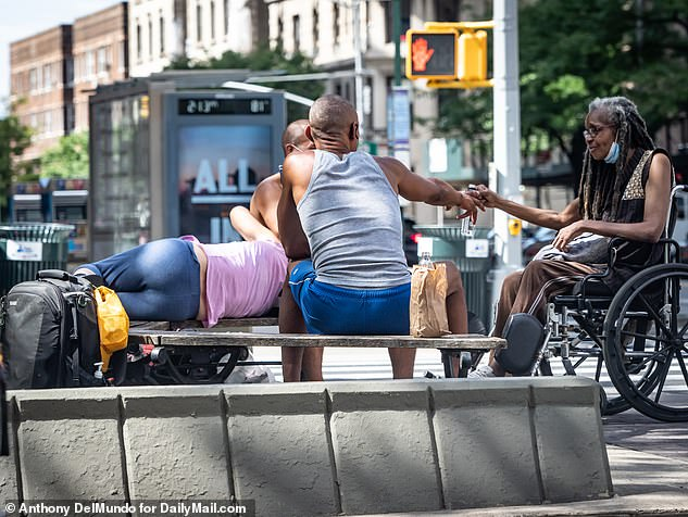 A group of presumably homeless people pass around a bottle of alcohol out in the open at the corner of W 79th Street and Broadway in the Upper West Side on September 3 amid outrage from locals who said Mayor Bill de Blasio's move to house homeless in hotels had led to their streets being overrun by drug use and public lewdness