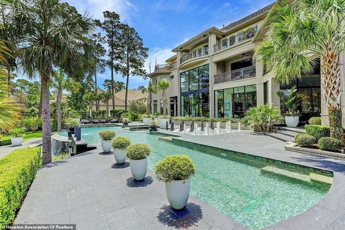 The backyard is studded with palm trees and features a massive swimming pool and oversized chess board