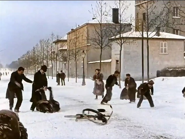 A cyclist who was riding his bike though the chaos loses his balance and falls on the road after being hit by a snowball