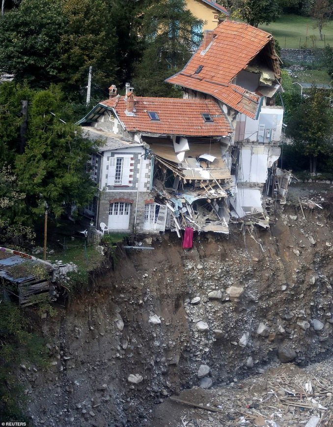 Roads were turned into raging torrents as floodwaters flowed down the mountains, sweeping away everything in their path - including half of this house in Saint-Martin-Vestubie, and the road outside