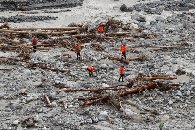 Firefighters and rescue workers search an area which used to be a road but has been left as little more than a rocky crater following Storm Alex, which dumped three months' of rain in just a few hours at the weekend