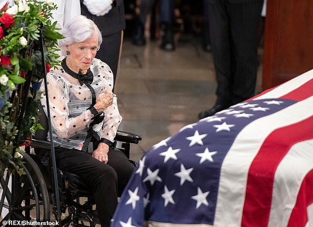 Roberta McCain makes the sign of the cross next to the casket bearing the remains of her son