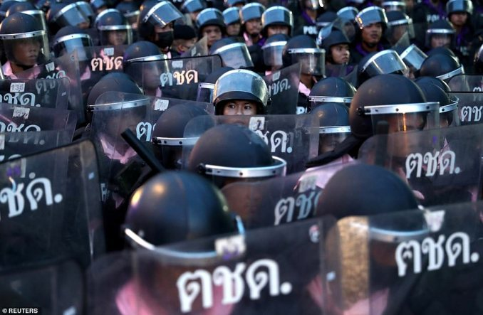 The decree also prohibits 'publication of news, other media, and electronic information that contains messages that could create fear or intentionally distort informationcreating misunderstanding that will affect national security or peace and order'. Pictured:Police officers stand in position during a protest in the early hours of Thursday morning in Bangkok