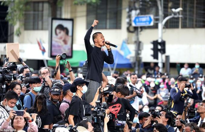 A man raises his fist in the air as he speaks during a protests in downtown Bangkok on Thursday, just hours after riot police cleared demonstrators off the streets