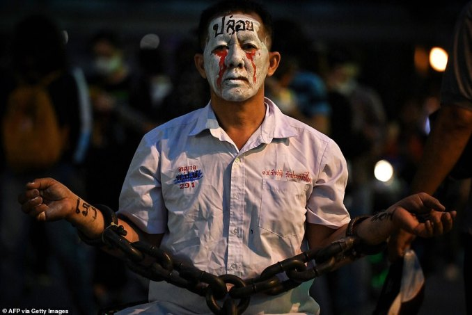 A pro-democracy protester wears chains and make-up during a demonstration at a road intersection in Bangkok today, after Thailand issued an emergency decree following an anti-government rally the previous day
