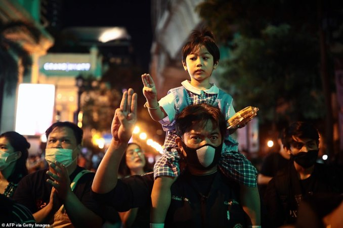 A pro-democracy protester and a child on their shoulders holds up the three-finger salute during a demonstration in Bangkok today, after Thailand issued an emergency decree following an anti-government rally the previous day