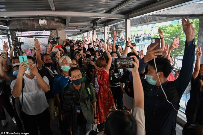 Pro-democracy protesters hold up the three-finger salute as they gather on a crosswalk in Bangkok