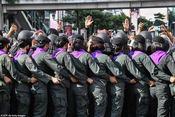 Police line up in front of pro-democracy protesters gathering for a rally on a traffic intersection in Bangkok