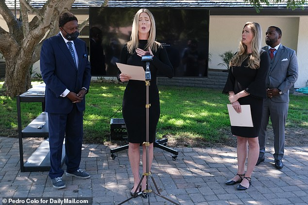 Kirsten Ely speaks at the press conference, flanked by her sister Kaitland (right), and attorneys John L. Burris (far left), and DeWitt M. Lacy (far right)