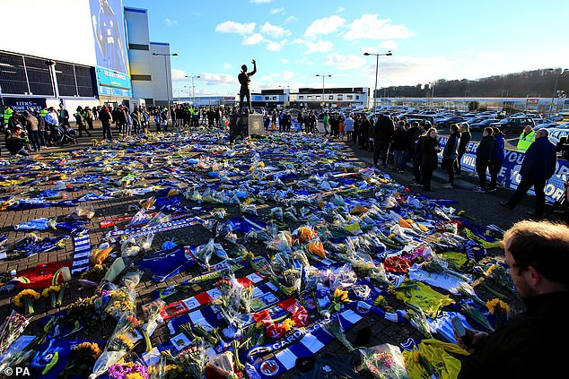 Fans look at the flowers placed outside Cardiff City Stadium in tribute to Sala - who never played for his new club - on February 2 last year