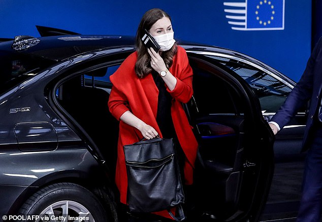 Marin, wearing a mask, gets out of a car while speaking on her phone as she arrives for the second day of the summit today
