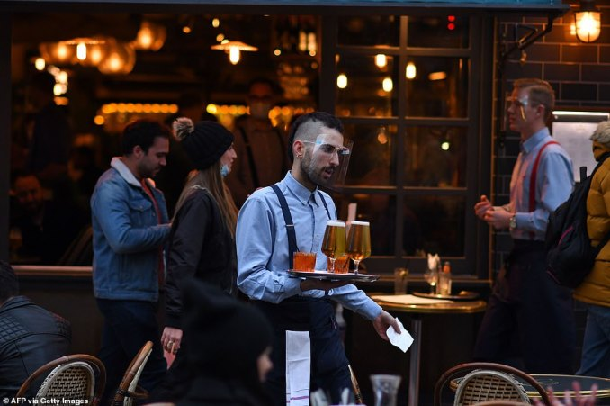 Further anger has stemmed from data revealing Devon, Oxford and Coventry all have higher coronavirus infection rates than London but will face no lockdown rules when the capital moves into Tier Two tomorrow. Pictured, a waiter brings customers' their drinks in Soho