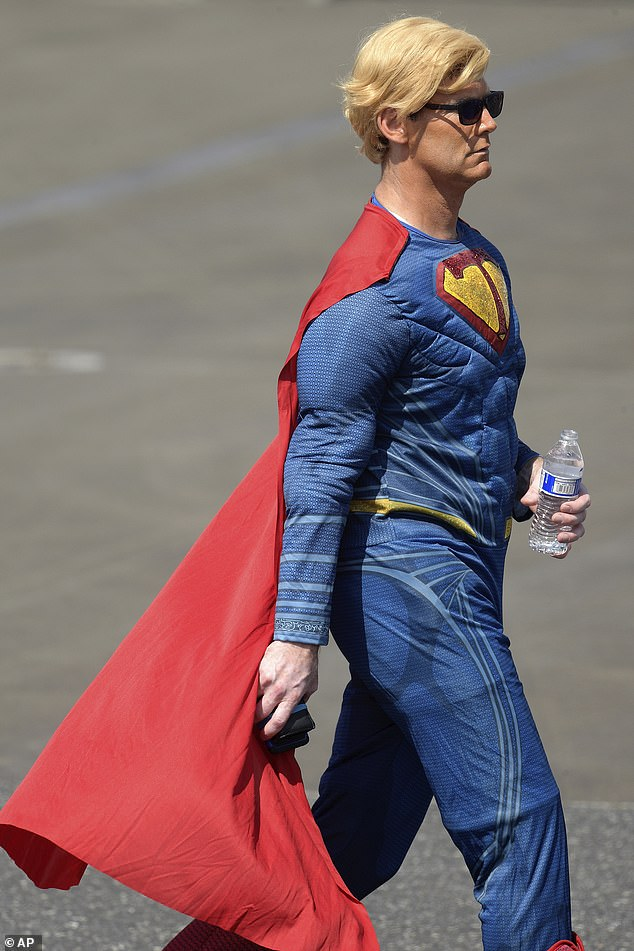 A supporter of President Donald Trump dressed as Superman walks on the tarmac at the Ocala International Airport