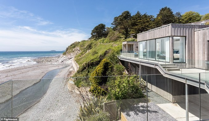 This impressive wood-clad waterside home, on the market for £3.5million with John Bray & Partners, is nestled on the south coast of Cornwall and comes with sublime ocean views and private access to the beach