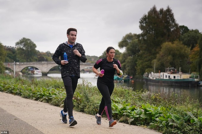 Exercise classes and organised sport can continue to take place outdoors under the Tier 2 restrictions. Pictured: Runners out for fresh air along the Thames