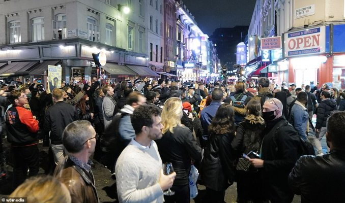 Some revellers took their drinks with them into the street. One man was pictured holding a wine glass as demonstrators complained about the harsh restrictions behind him