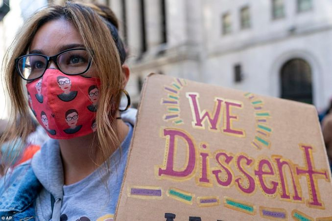 Several demonstrators wore face masks honoring the late Justice Ruth Bader Ginsburg on Saturday. The image above shows a protester holding a sign that reads 'We dissent'