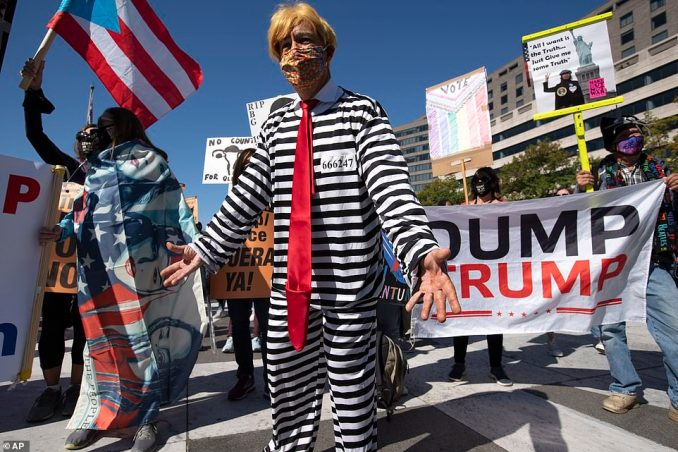 One demonstrator is seen dressed up in a prison uniform while wearing a wig and a tie meant to depict President Trump in Washington, DC, on Saturday