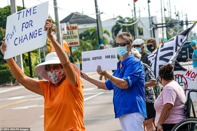 Dozens of demonstrators held signs as motorists drove by in Fort Myers, Florida, on Saturday