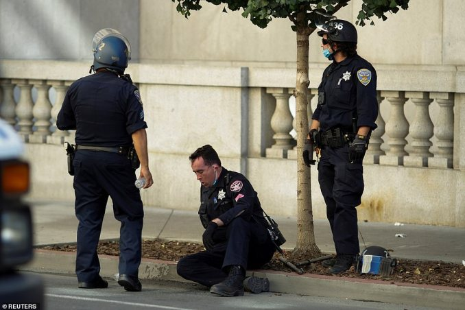 A San Francisco police officer is seen on the ground after suffering injuries during the clash
