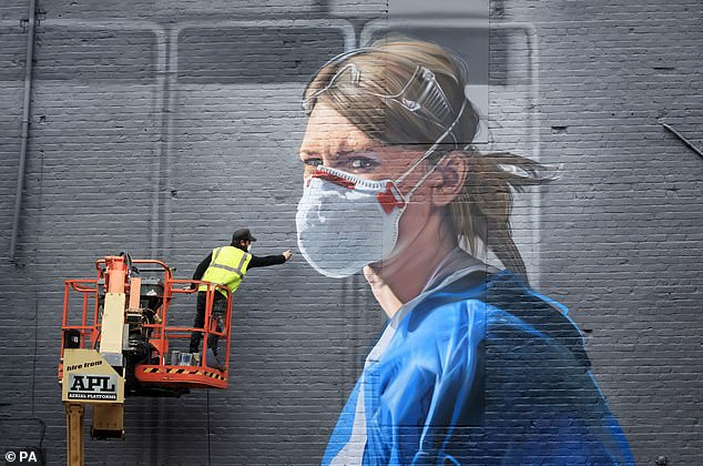 Artist Peter Barber works on a mural in Manchester city centre yesterday, depicting nurse Melanie Seniorafter The National Portrait Gallery commissioned the mural based on a photograph by Johannah Churchill