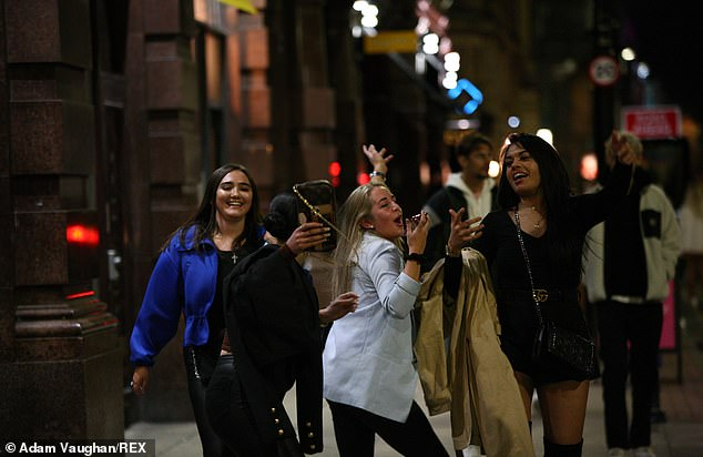 A group of women in Manchester sing as the 10pm curfew approached yesterday evening