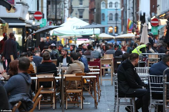 Crowds of people sit at tables placed on the streets of central London as the city faces stricter restrictions amid the pandemic