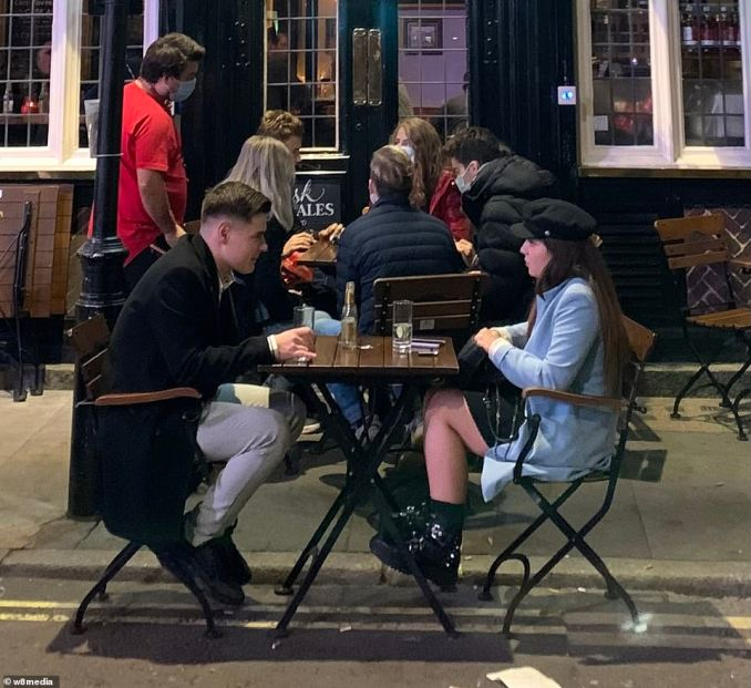A group of people sit outside as London heads into day two of the Tier Two lockdown. Under Tier Two restrictions, households are banned from meeting indoors, even in hospitality venues