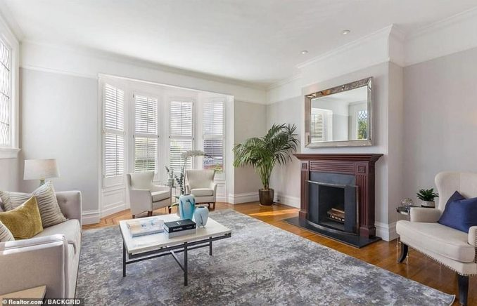 An adjoining living space, looking out onto the street, has a similar fireplace