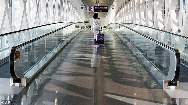 New data from the TSA shows that just 907,332 people passed through checkpoints on Thursday, which is down from 2,428,095 who did so at the same time last year - a 62 percent drop. Pictured:A traveler walks with her luggage across a nearly empty skyway bridge at Logan Airport, November 20