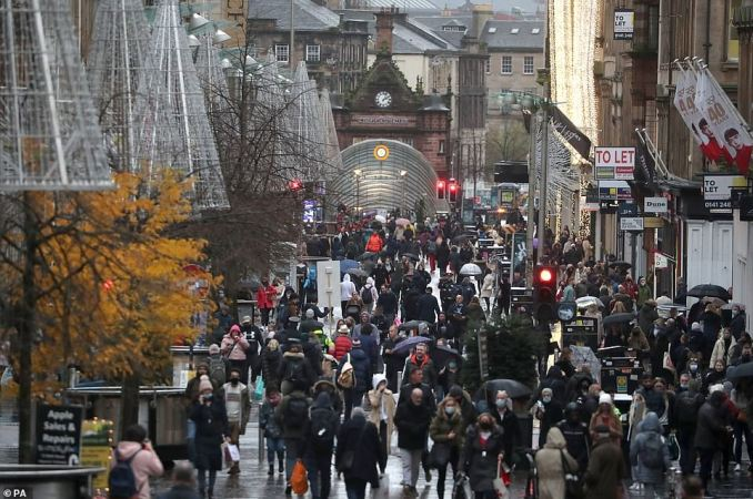 Christmas shoppers out and about in the rain on Buchanan Street in Glasgow today. Eleven local council areas in Scotland will move into Level 4 restrictions from 6pm this evening