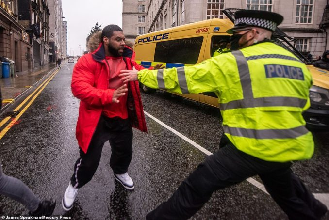 A man comes face to face with a police officer as scenes turned ugly during an anti-lockdown protest in Liverpool today