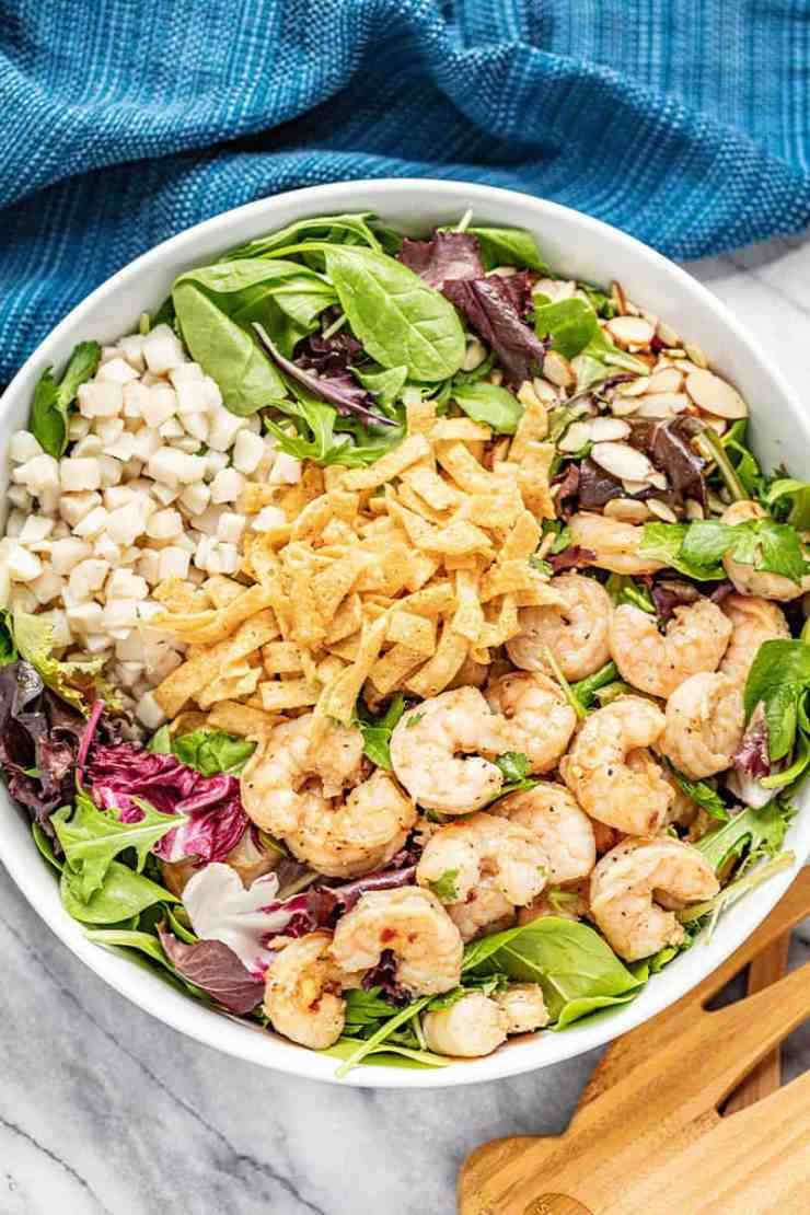 Thai Shrimp Salad topped with shrimp, crispy wonton strips, water chestnuts, cilantro, and leafy greens in a white bowl