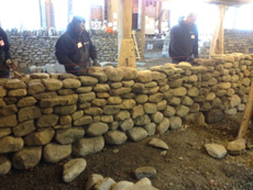 Dry stone wall workshop building the 2nd lift. Note the through stones